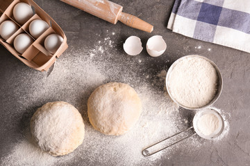 Raw dough with ingredients on kitchen table