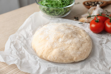 Raw dough with ingredients for pizza on kitchen table