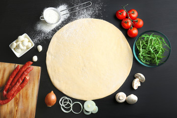 Raw dough for pizza with ingredients on kitchen table