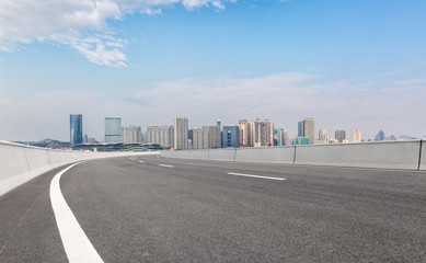 cityscape and skyline of zhengzhou in China from empty asphalt road in the daytime