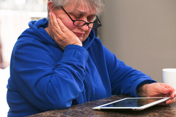 Beautiful, Mature, Elder, Grandmother, Woman with Grey Hair, in Eyeglasses is Using a Digital Tablet, Sad, Angry, at home