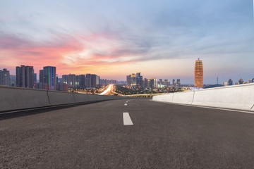 empty asphalt road and modern buildings in Zhengzhou east new district at twilight