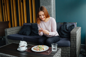Young woman taking picture of food with smartphone posting on social media