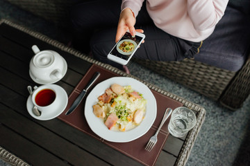 Girl hand holding smartphone and taking photo of food on wooden table. Top view.