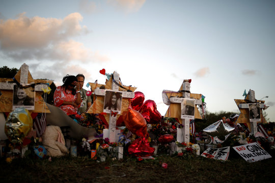 People grieve in front of Stars of David placed in front of the fence of the Marjory Stoneman Douglas High School to commemorate the victims of the mass shooting, in Parkland