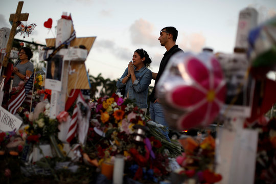 People mourn in front of crosses and Stars of David placed in front of the fence of the Marjory Stoneman Douglas High School to commemorate the victims of the mass shooting, in Parkland