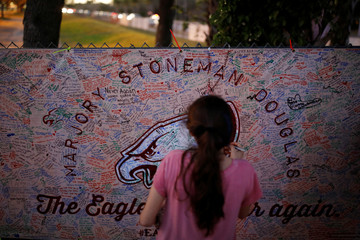A girl writes a note on a banner placed on the fence of the Marjory Stoneman Douglas High School to commemorate the victims of the mass shooting, in Parkland
