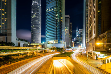 Traffic at central district in Hong Kong at dusk time. Car light trails and urban landscape in Hong Kong .