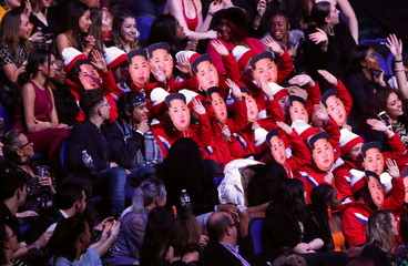 Spectators wear Kim Jong-un masks as they impersonate the North Korean cheerleaders at the Winter Olympic Games at the Brit Awards at the O2 Arena in London