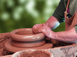 Hands of a Potter doing pottery on a Potter's wheel on the green background.