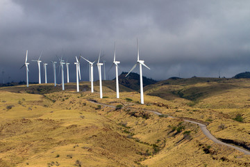 A wind farm rises above Honoapillani Highway 30 as it passes along Papawai Point on Maalaea Bay on the northwest coast of Maui, shot from a boat in the bay