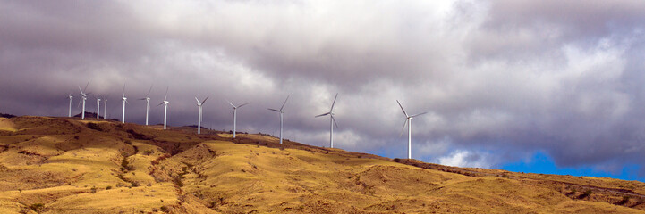 Panorama of a wind farm above Honoapillani Highway 30 as it passes along Papawai Point on Maalaea Bay on the northwest coast of Maui, shot from a boat in the bay