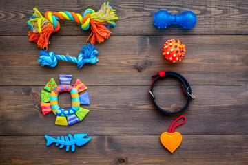 Pet accessories. Toys near collar on dark wooden background top view