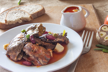 Moroccan dish of fried chicken hot liver in a plate with a spicy vegetable sauce on the table