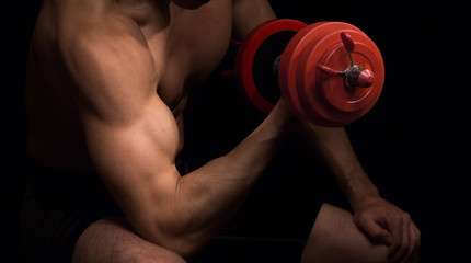 Man with red dumbbell on black background, bodybuilding concept