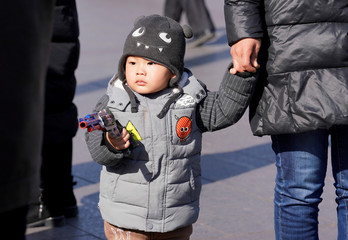 A boy is seen at Beijing Railway Station during the Chinese Lunar New Year travel rush in Beijing