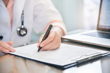 female doctor is using laptop and writing something on clipboard.