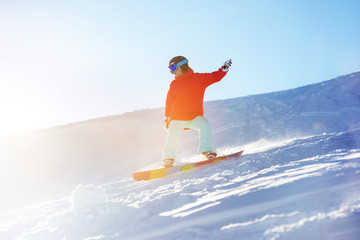 Lady snowboarder at ski slope in sun light