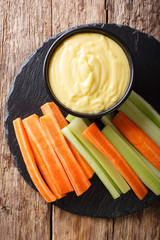 Healthy food: cheese cream sauce dip with fresh vegetables close-up. Vertical top view
