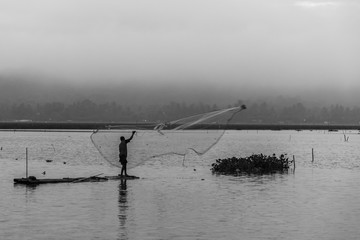 Black and white photo of fisherman in foggy misty morning.