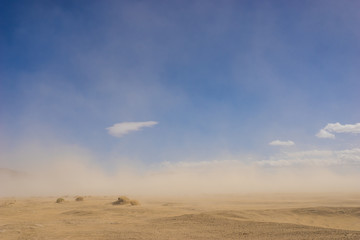 Wide sand desert in drought climate covered by a windy sandstorm.