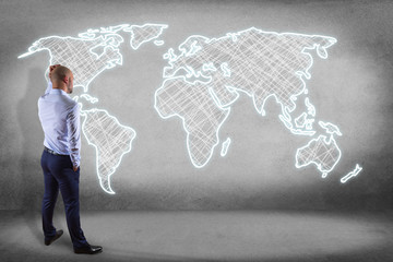 Businessman in front of a wall with a Hand drawn world map on a futuristic interface