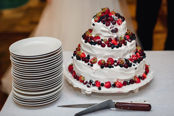 white cream wedding cake with fresh sweet strawberries, cherries, blueberries, black currants with three tiers on the table with plates