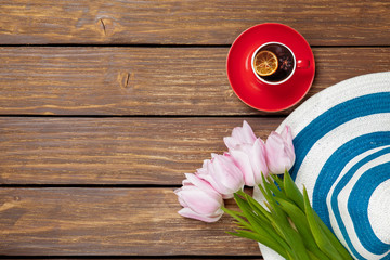 Cup of english tea with spring tulips and hat