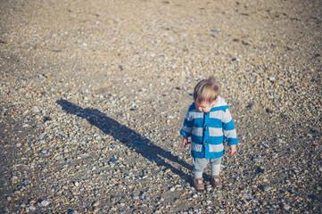 Cute little boy standing on the beach in winter