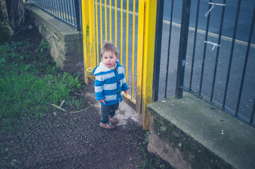 Little boy standing by the gate of a playground