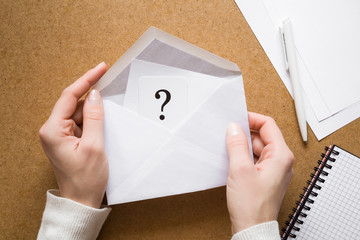 Woman's hands holding an opened envelope with question mark. Getting an answer, results or bill through a post letter. Received message concept.