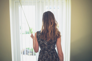 Young woman opening blinds