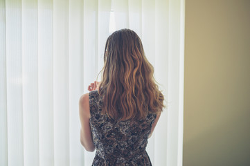 Young woman peaking through blinds