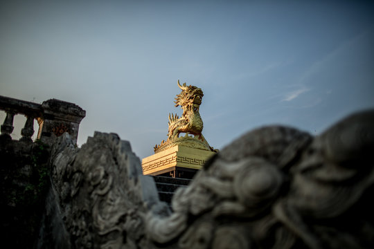 A gold colored dragon statue inside the Citadel in Hue, Vietnam.