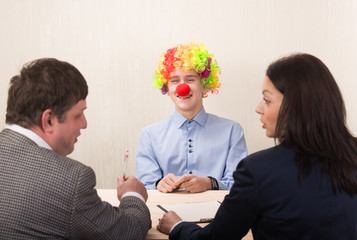 Funny portrait of young man during job interview and members of managemen