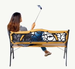 Back view of a woman to make  selfie stick portrait sitting on the bench.