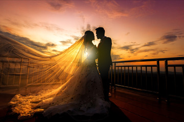 silhouette of wedding Couple in love kissing and holding hand together during sunset with evening sky background