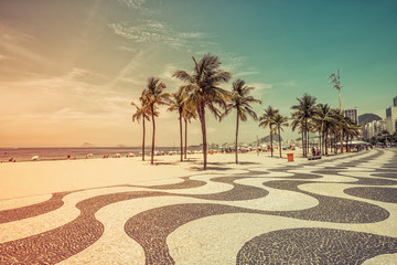 Sunny day with palms by Copacabana Beach mosaic boardwalk, Rio de Janeiro. Vintage colors with light leak