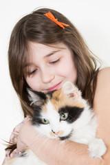 Caucasian girl hugging cat on white