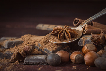Chocolate, Spices, Spoon with Cocoa, Hazelnut on the Wooden Background. Copy space
