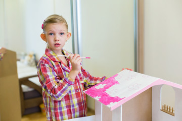 little girl is painting a house for dolls
