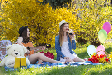 Beautiful young women in park, sitting on a blanket, playing guitar, drinking wine, relaxing and enjoying a nice picnic day. Spring and summer lifestyle concept