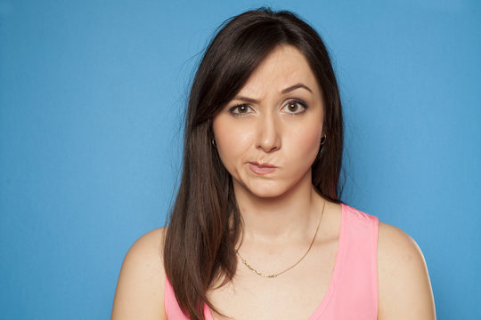 young woman looks suspiciously on a blue background