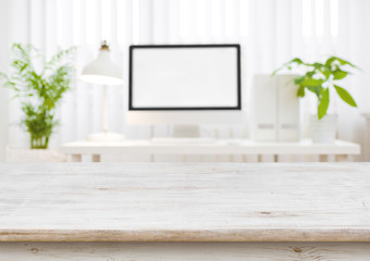 Wooden table top with blurred modern working place as background