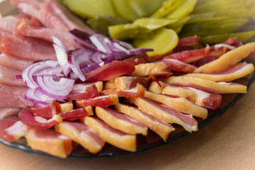 Close-up of ham, bacon, lettuce, cucumber and onion on paper, on a platter