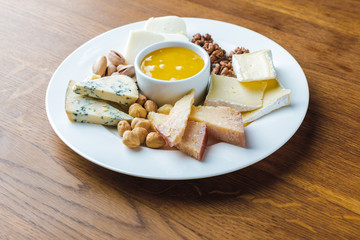 close-up view of delicious cheese plate with nuts and honey on wooden tabletop