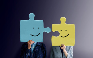 Happiness Couple or Business Partnership Concept. Portrait of two People with Happy Face Emotion on Jigsaw Puzzles