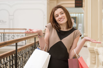 Young beautiful happy woman in a shopping center with shopping in colored paper bags