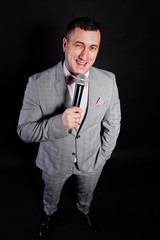 Handsome man in gray suit with microphone against black background on studio.  Laughs face of toastmaster and showman.