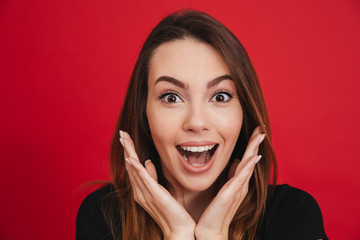 Portrait of pretty woman 20s holding arms at face and smiling broadly, isolated over red background